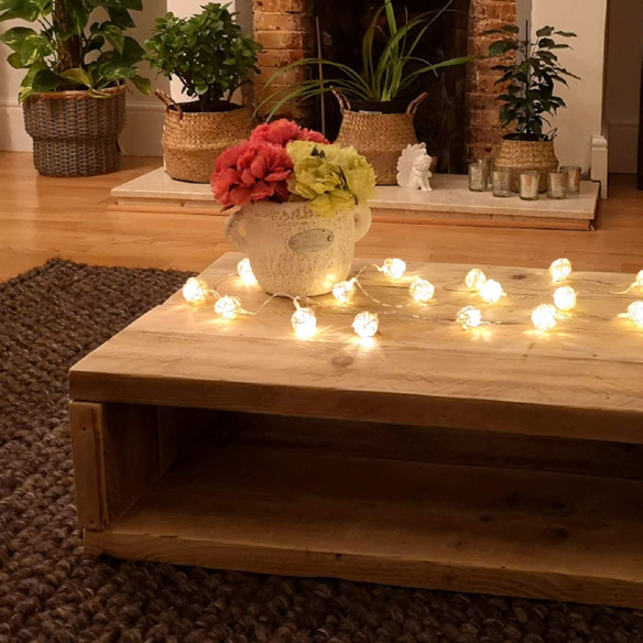 A flower pot on a table with fairy lights