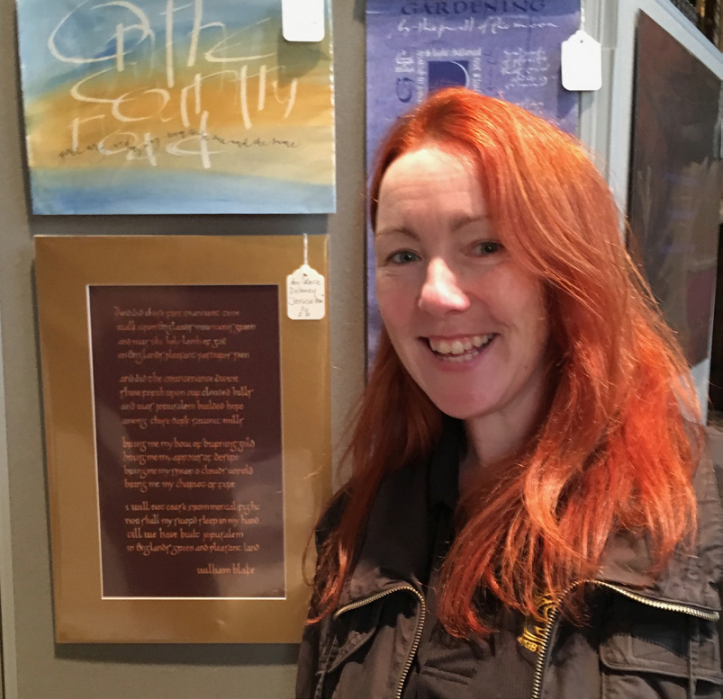 Anne Marie Delaney, from SMI, standing next to her calligraphy art work
