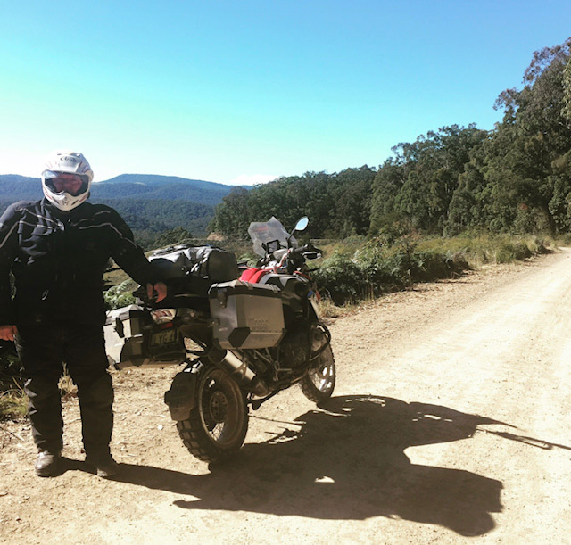 SMI team member with a motorbike on a dirt road