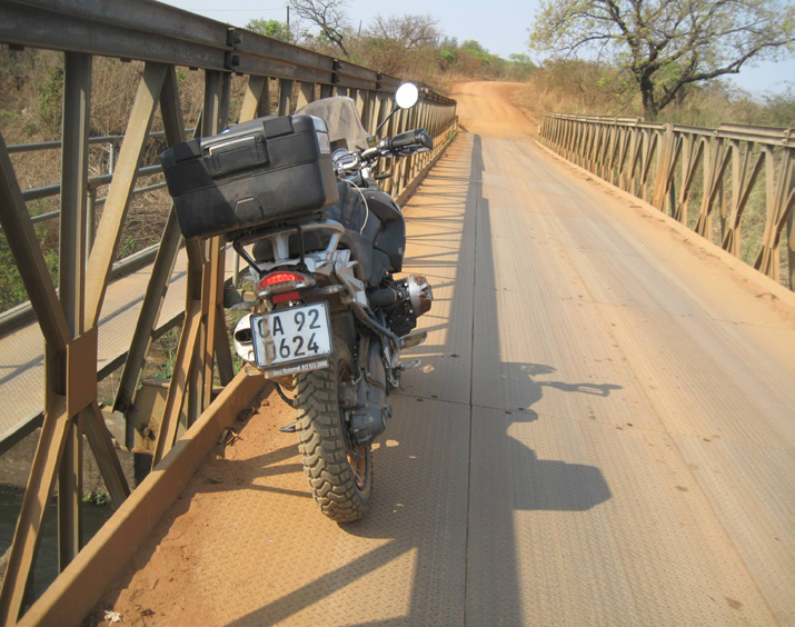 Motorbike leaning on the rails of a bridge